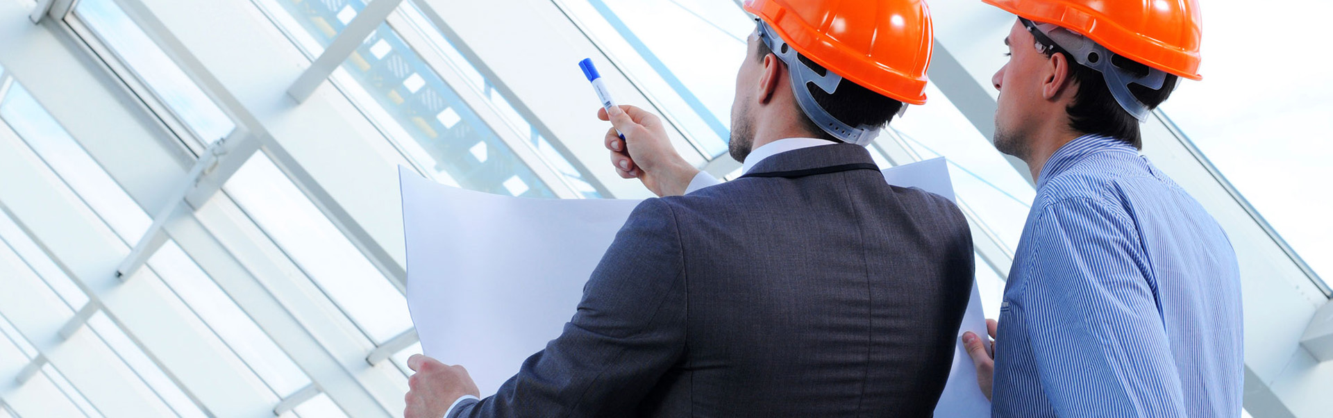 Construction manager checking project details with worker.