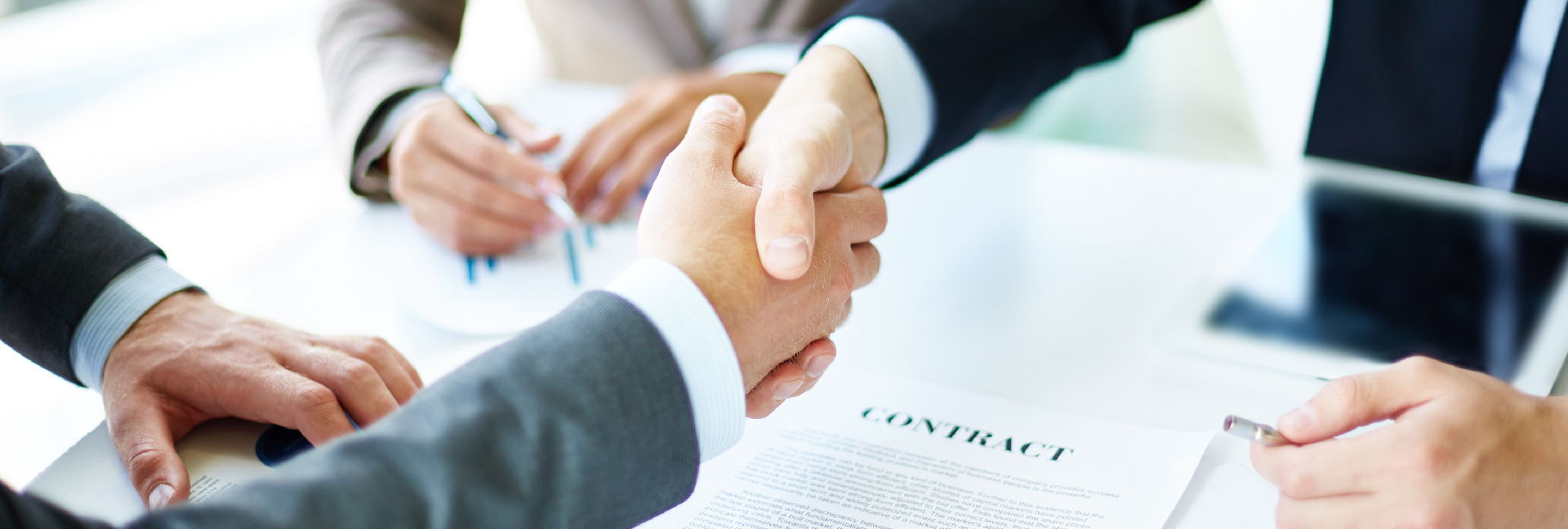 Two business professionals shake hands over an international trade contract.