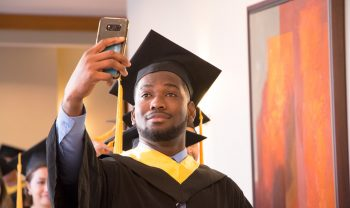 Brighton College graduate of 2018 taking a selfie before entering the ceremony processional.